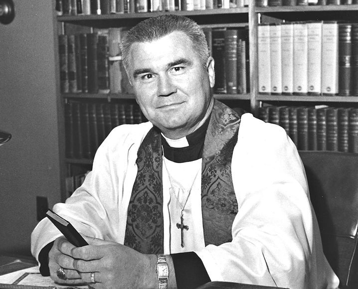 Black and white photo of Faith International's first president Dr. R.H. Redal sitting in pastoral attire in front of a bookcase.