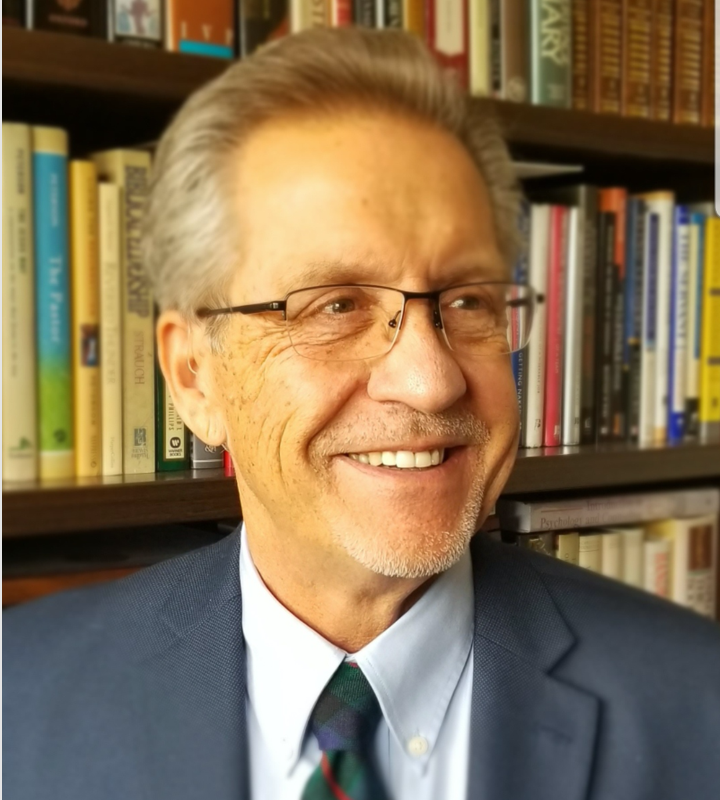 Current Faith International University president Dr. Michael J. Adams smiles while standing in front of a bookcase.
