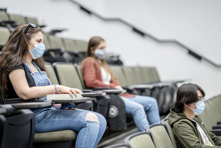 Students social distance in a classroom while wearing face masks.